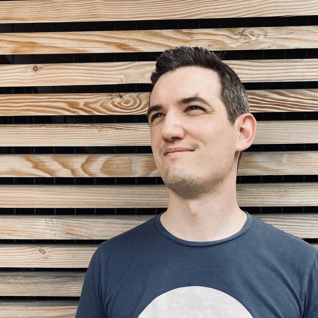 Bild von Autor Tom Maurer, mäßig frisiert und aufrecht stehend, vor einer Wand aus Holzlatten. Brett hinterm Kopf ist einfach die bessere Alternative. Dieser Text ist für SEO und Co.